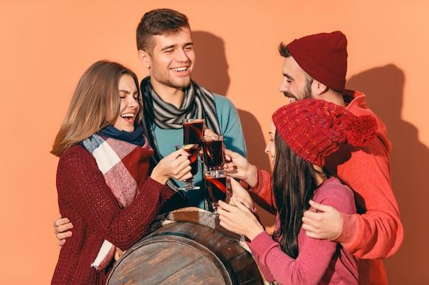 Homens e mulheres europeus sorridentes durante a sessão de fotos da festa. os caras se passando por amigos no festival de estúdio com uma taça de vinho com vinho quente quente em primeiro plano.