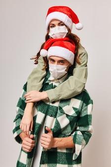Homens e mulheres felizes com chapéus de ano novo e máscaras médicas