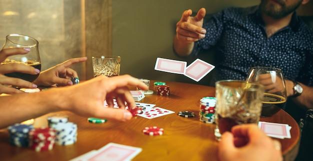 Homens e mulheres jogando jogo de cartas. conceito de pôquer, entretenimento noturno e emoção