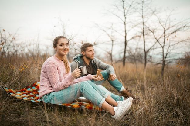 Homens e mulheres jovens fazem piquenique ao ar livre