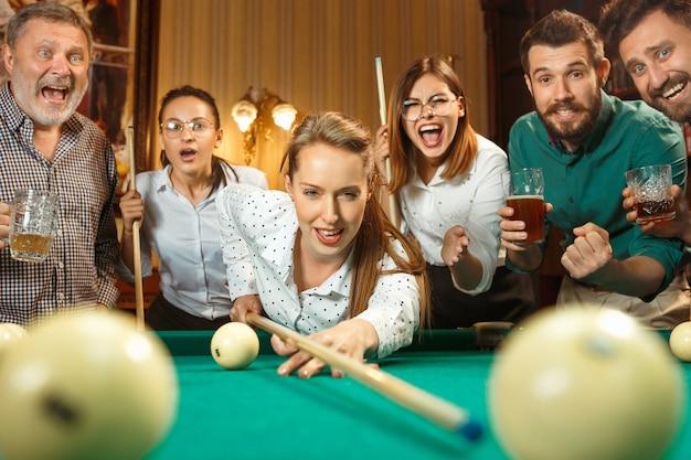 Homens e mulheres jovens jogando bilhar no escritório, depois do trabalho.