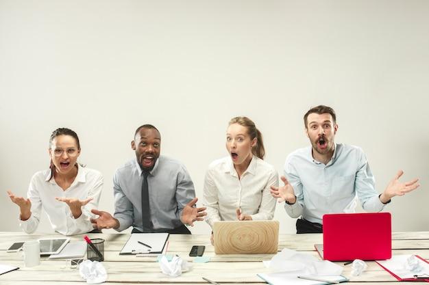 Homens e mulheres jovens sentados no escritório e trabalhando em laptops. conceito de emoções