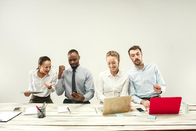 Homens e mulheres jovens sentados no escritório e trabalhando em laptops.