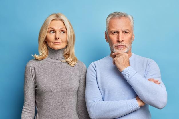 Homens e mulheres maduras sérias estão próximos um do outro e têm expressões atenciosas, vestidos com roupas casuais isoladas sobre a parede azul