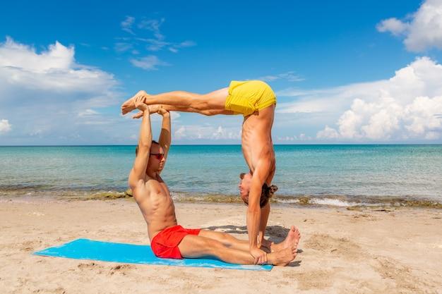 Homens e mulheres na praia fazendo exercícios de ioga e fitness juntos