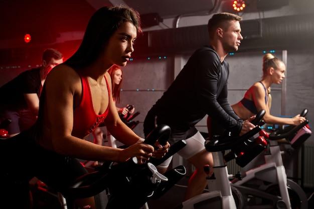 Homens e mulheres pedalando na academia, exercitando as pernas fazendo exercícios aeróbicos, pedalando em bicicletas, girando na academia de ginástica, vestindo macacão esportivo