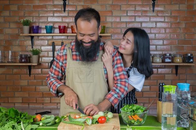 Homens e mulheres que estão cozinhando na cozinha com paredes de tijolo vermelho.