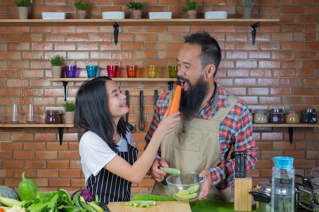 Homens e mulheres que se provocam enquanto cozinham na cozinha com uma parede de tijolos vermelhos.