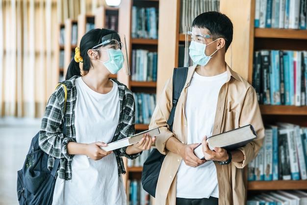 Homens e mulheres que usam máscaras estão de pé e leem na biblioteca.