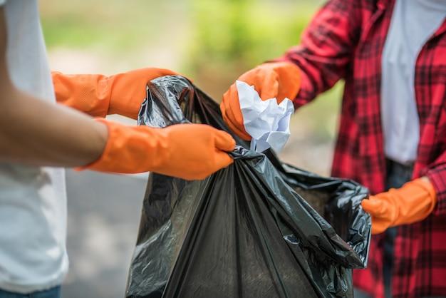 Homens e mulheres se ajudam a coletar lixo.