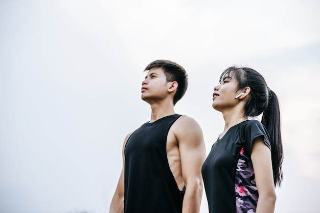 Homens e mulheres se levantam e olham para o céu após o exercício.