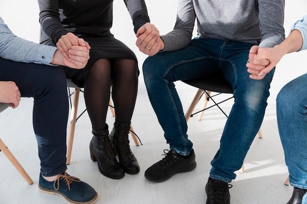 Homens e mulheres sentados em cadeiras e de mãos dadas