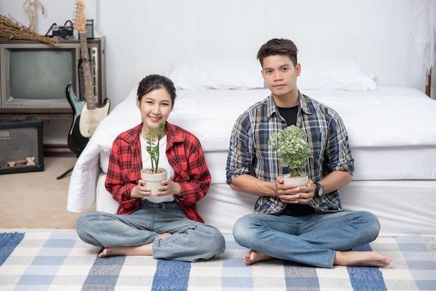Homens e mulheres sentam e segurando vasos de plantas em casa.