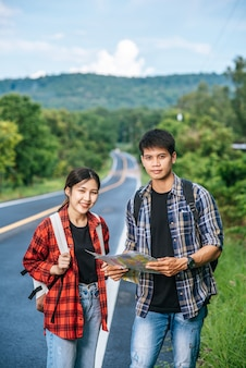Homens e mulheres turistas ficam para ver o mapa na estrada.