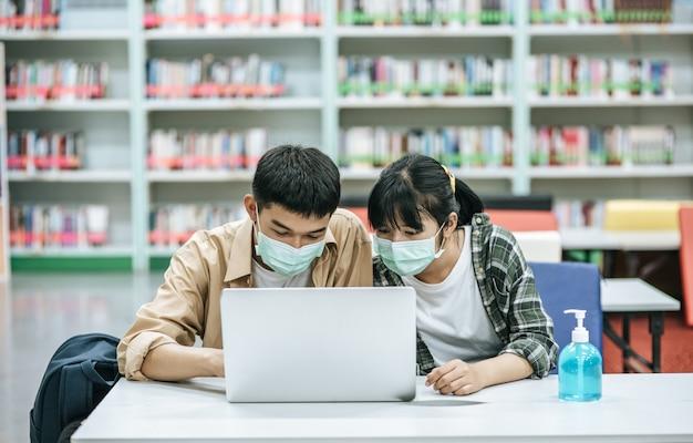 Homens e mulheres usam máscaras e usam um laptop para procurar livros na biblioteca.