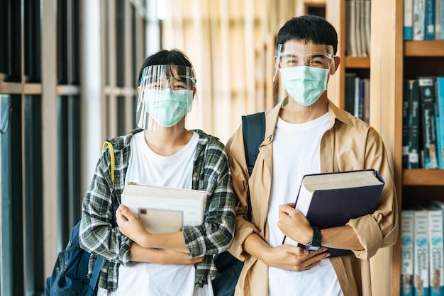 Homens e mulheres usam máscaras para segurar livros na biblioteca.