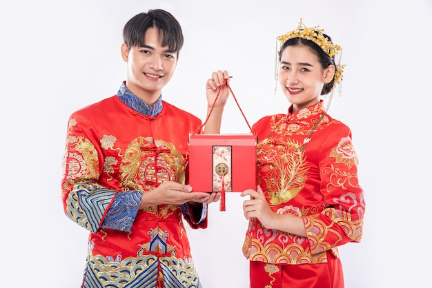 Homens e mulheres usando cheongsam em pé com bolsas vermelhas