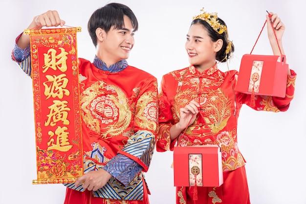 Homens e mulheres usando cheongsam em pé, segurando cartazes de saudação e carregando sacolas vermelhas