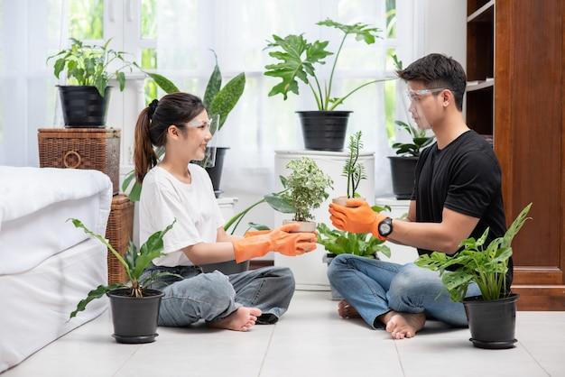 Homens e mulheres usando luvas laranja sentavam e plantavam árvores em uma casa.