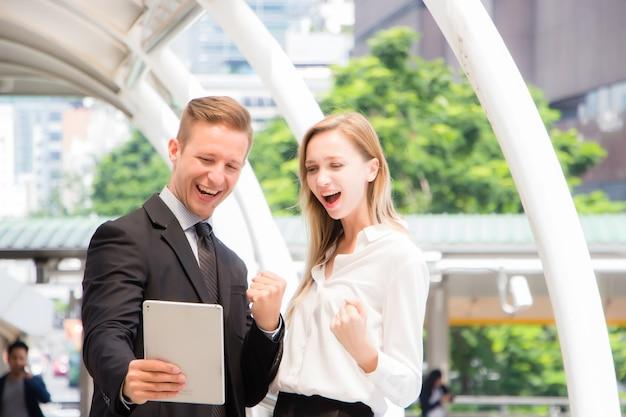 Homens e mulheres vestindo roupas formais eles olhavam para o tablet com rostos sorridentes e felizes.