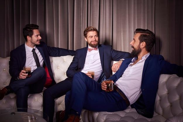 Homens elegantes com uísque em boate