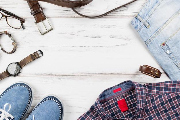 Homens elegantes roupas casuais e acessórios em fundo de madeira.