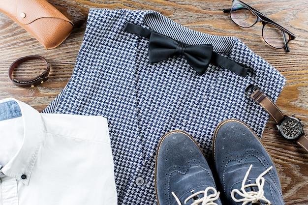 Homens elegantes roupas casuais e acessórios na mesa de madeira