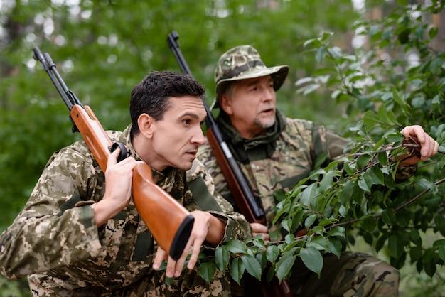 Homens em camo com rifles emboscados e esperando