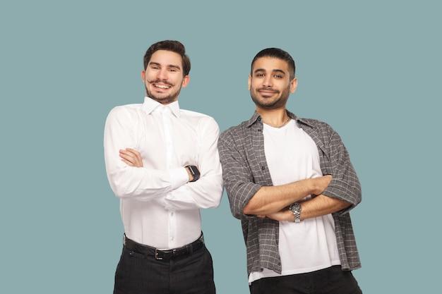 Homens em pé com as mãos cruzadas e olhando para a câmera com um sorriso cheio de dentes