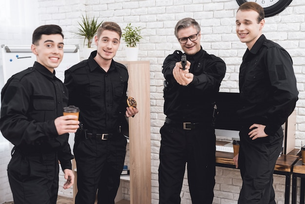 Homens em pé sorrindo sozinhos, apontando uma arma.