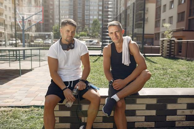 Homens em roupas esportivas descansam após o treino em um parque