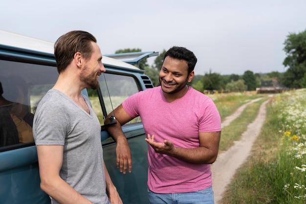Homens em tiro médio conversando perto da van