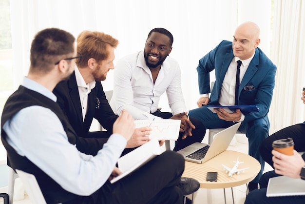 Homens em trajes discutem problemas de trabalho.