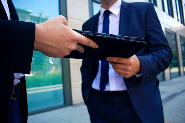 Homens entregam uns aos outros nas mãos de um livro eletrônico