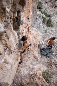 Homens escalando montanha com equipamentos de segurança
