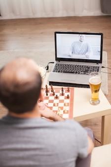 Homens espertos jogando xadrez em videochamada durante a quarentena.
