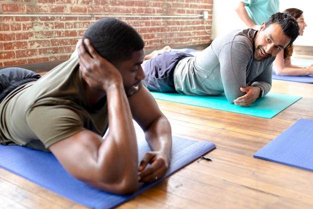 Homens esportivos relaxando em tapetes de ioga