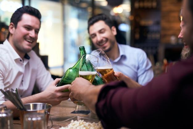 Homens fazendo uma torcida no bar