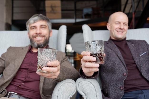 Homens felizes e bem-sucedidos em roupas da moda sentados em poltronas e bebendo álcool juntos