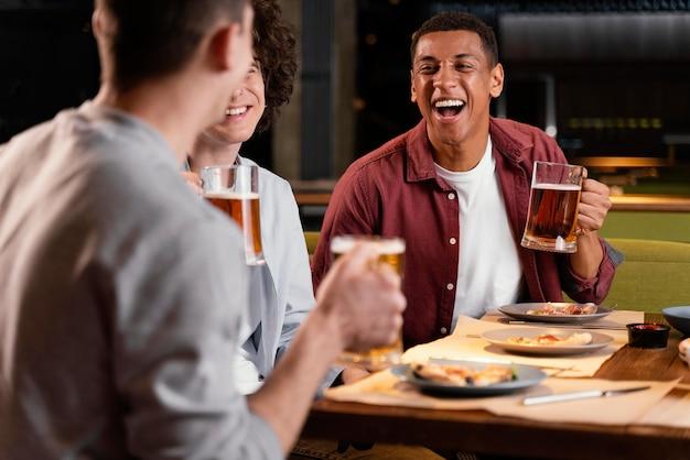 Homens felizes em close com canecas de cerveja
