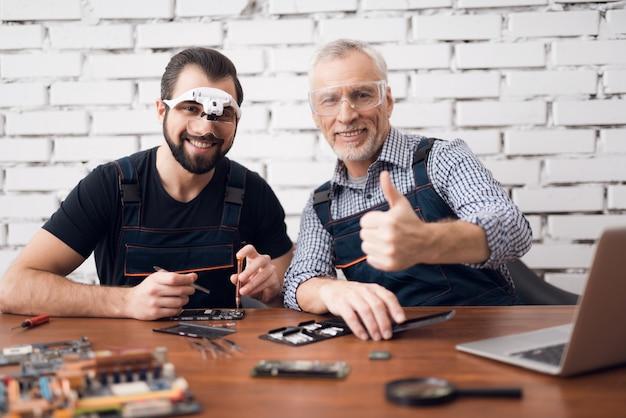 Homens felizes que testam os componentes do portátil que fixam o dispositivo.