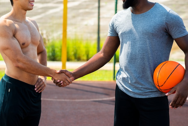 Homens fortes apertam as mãos plano médio