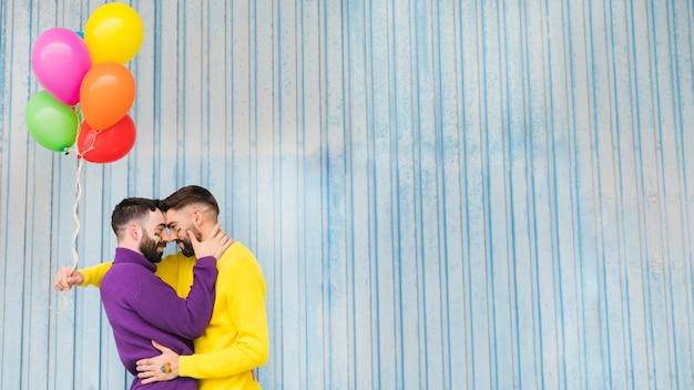 Homens gays abraçando e segurando balões coloridos