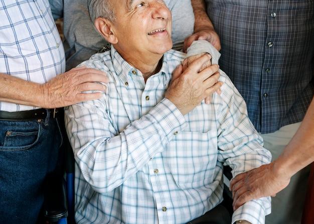 Homens idosos alegram seu amigo em uma cadeira de rodas