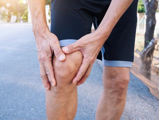 Homens idosos asiáticos com dor no joelho e dor muscular do exercício com a execução.