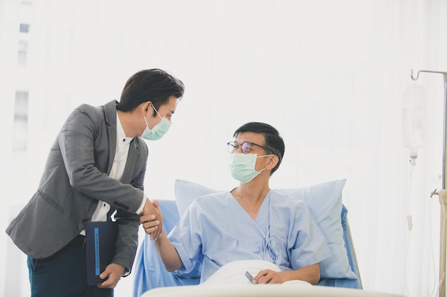 Homens idosos deitados na cama na reunião do hospital com consultor financeiro, mulher sênior lendo contrato. ambos usavam máscaras de higiene para evitar surtos de doenças.