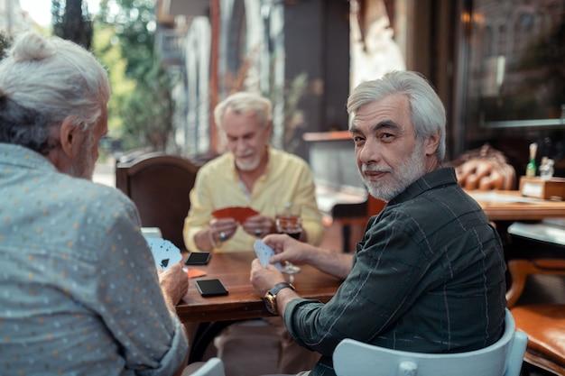 Homens idosos jogando. homens idosos de cabelos grisalhos aposentados jogando sentados do lado de fora do bar