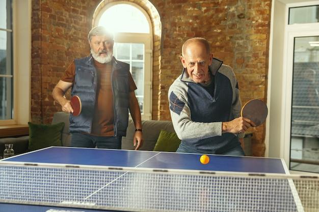 Homens idosos jogando tênis de mesa no local de trabalho, se divertindo. amigos com roupas casuais jogam pingue-pongue juntos em um dia ensolarado. conceito de atividade de lazer, esporte, amizade, teambuilding, trabalho em equipe.