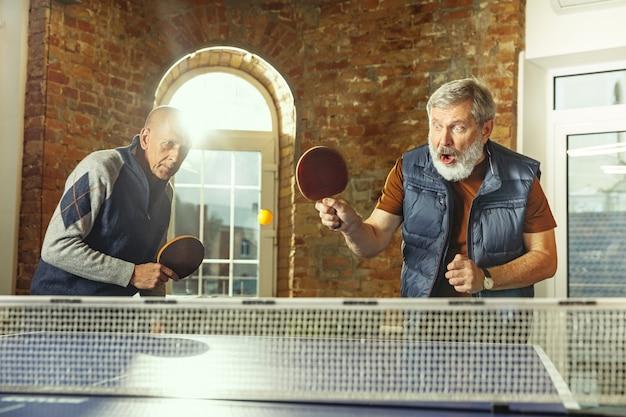 Homens idosos jogando tênis de mesa no local de trabalho se divertindo