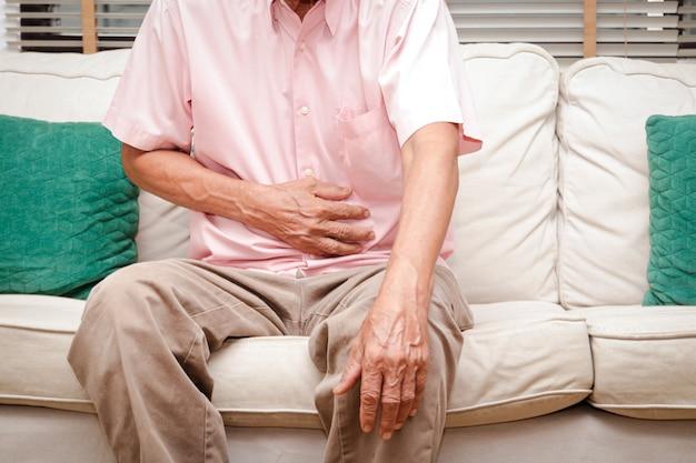 Homens idosos têm dor abdominal sentados no sofá da casa